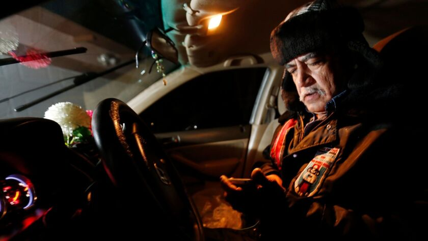 LANCASTER, CA – FEBRUARY 13, 2018: Jorge Alcala checks his phone as he sits in his car warming up