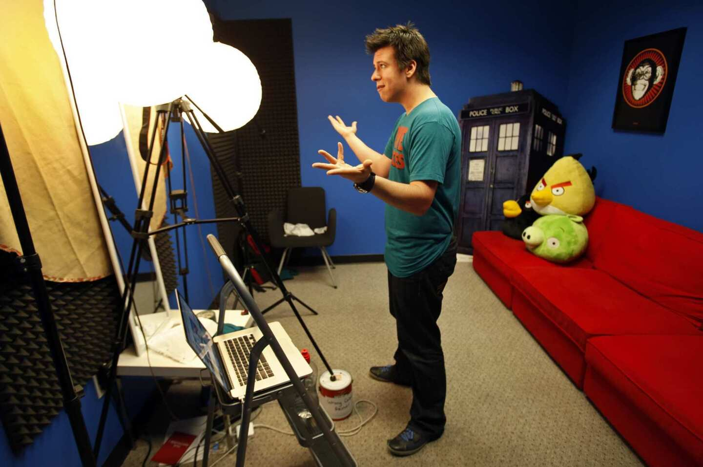 """Philip DeFranco delivers his lines to his camera during a run-through Aug. 21 in the simple studio of his Woodland Hills production offices where he records his show as host of the """"The Philip DeFranco Show,"""" a news program on YouTube about news and pop culture. The show rivals Jon Stewart's """"The Daily Show"""" in audience size. As the news anchor, DeFranco wears T-shirts instead of the standard-issue suit-and-tie, and the anchor desk has been replaced with a red futon decorated with stuffed characters."""
