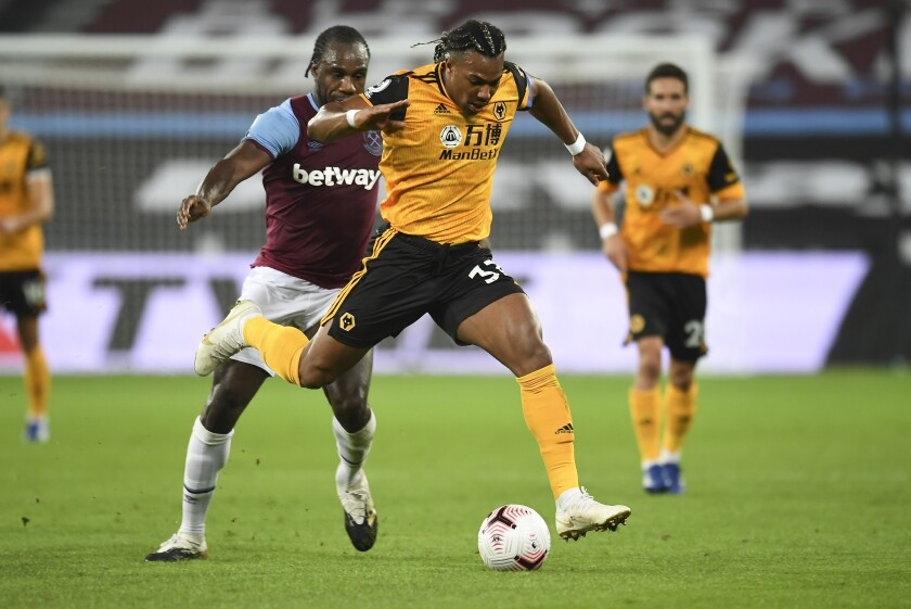 Wolverhampton Wanderers' Adama Traore, right, battles for the ball with West Ham's Angelo Ogbonna during the English Premier League soccer match between West Ham and Wolverhampton Wanderers at London Stadium, London, England, Sunday, Sept. 27, 2020. (Andy Rain/Pool via AP)