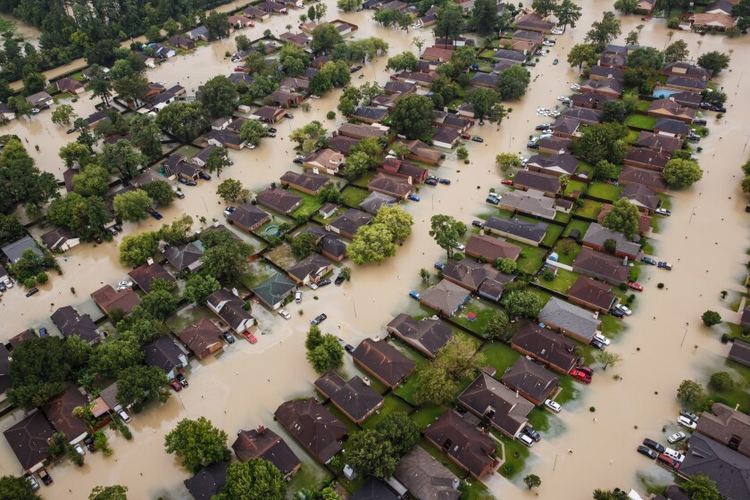 Water from Addicks Reservoir flows into neighborhoods as floodwaters from Tropical Storm Harvey rise Tuesday.
