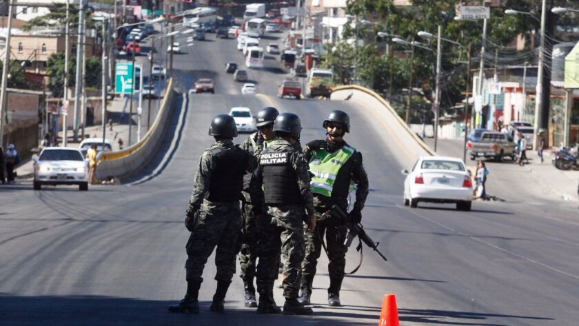 Soldiers monitor a check point in Tegucigalpa, Honduras, Saturday, Dec. 2, 2017. At least one opposi