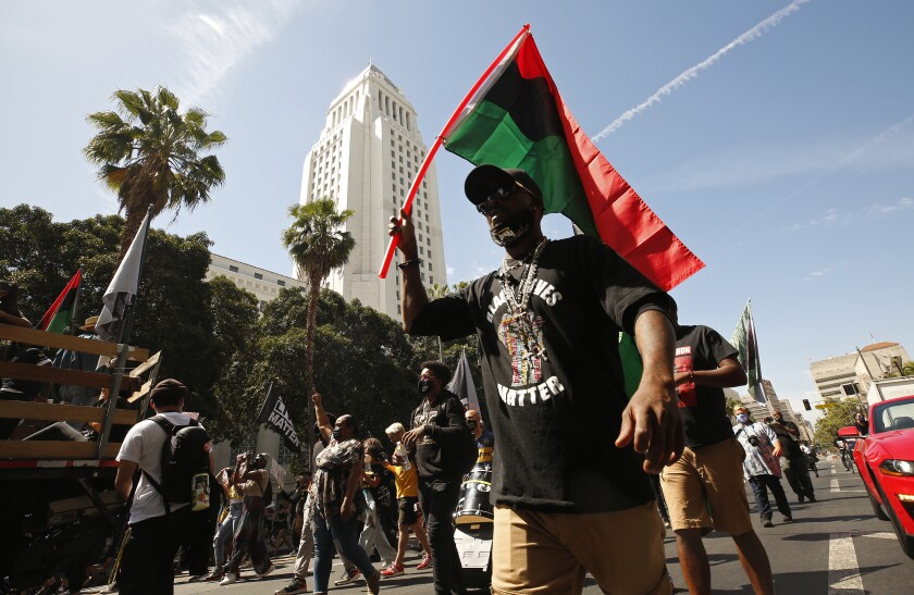 A man in a Black Lives Matter T-shirt and holding a Pan-African flag walks with other people down a city street.