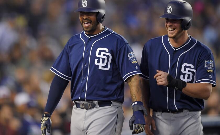 Los jugadores de los Padres de San Diego, Matt Kemp (i) y Wil Myers, celebran un doble de Melvin Upton Jr. en el quinto inning de su juego contra los Dodgers en Los Ángeles.