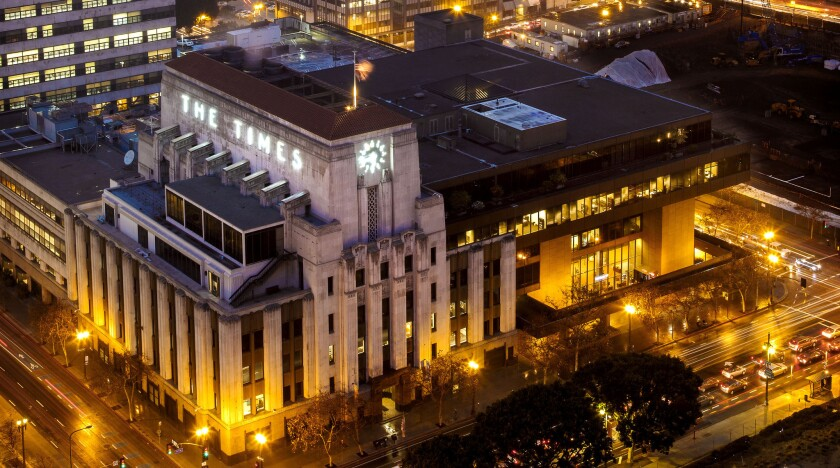 """An Art Deco building in downtown Los Angeles with the words """"The Times"""" in lights on its side"""