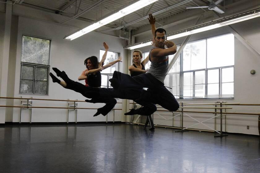 "Miguel Perez (right), Lillian Barbeito (middle/blond hair), Tina Finkelman Berkett (left/dark hair), and Andrew Wojtal (hidden from view) of BodyTraffic rehearse Richard Siegal's ""o2Joy"" at the Loyola Marymount University Dance Department."