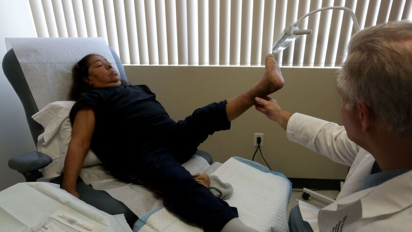 Dr. Stanley Mathis examines Maria Valdez, a diabetic who underwent surgery to save her foot when it became infected so she could avoid amputation.