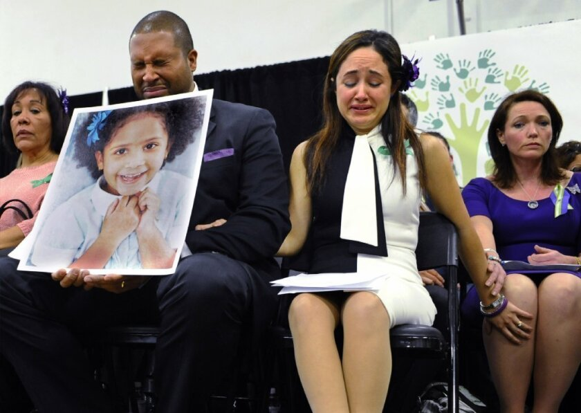 Jimmy Greene, foreground left, and Nelba Marquez-Greene, center, the parents of Sandy Hook Elementary School shooting victim Ana Marquez-Greene, shown in the large photograph; and Nicole Hockley, right, mother of victim Dylan Hockley, react during a news conference at Edmond Town Hall in Newtown, Conn., in January.