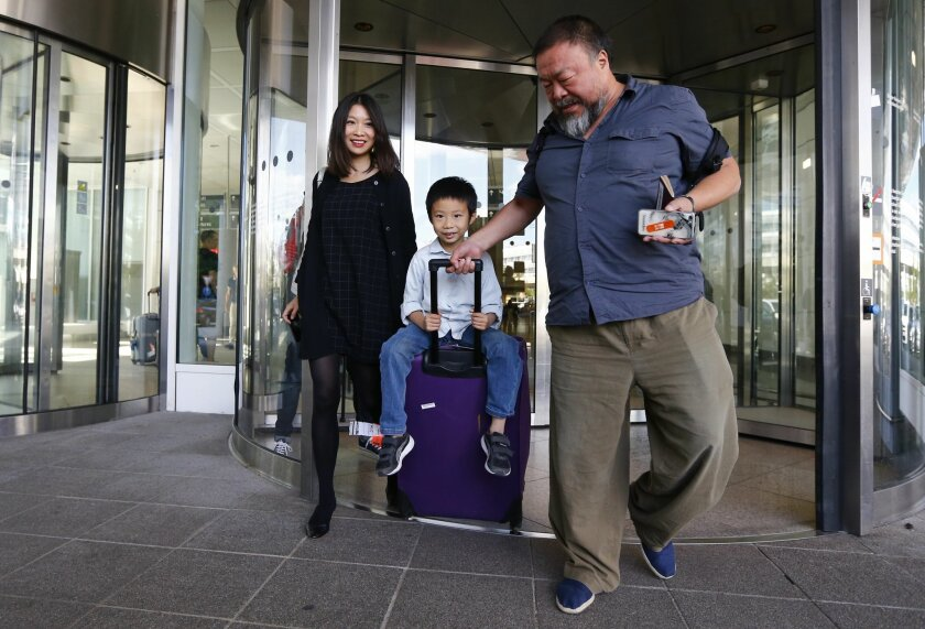 Chinese dissident artist Ai Weiwei, right, his wife Lu Qing, left, and his son Ai Lao arrive at the airport in Munich, Germany, Thursday, July 30, 2015. Ai Weiwei is on his way to Berlin where part of his family lives. (AP Photo/Matthias Schrader)
