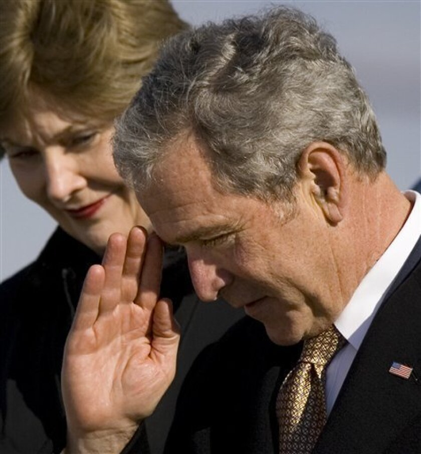 President George W. Bush salutes as he and first lady Laura Bush step down from Air Force One after a quick trip to Philadelphia where they marked the anniversary of his No Child Left Behind law with a visit to a local school, at Andrews Air Force Base, Md., Thursday, Jan. 8, 2009. (AP Photo/J. Sco