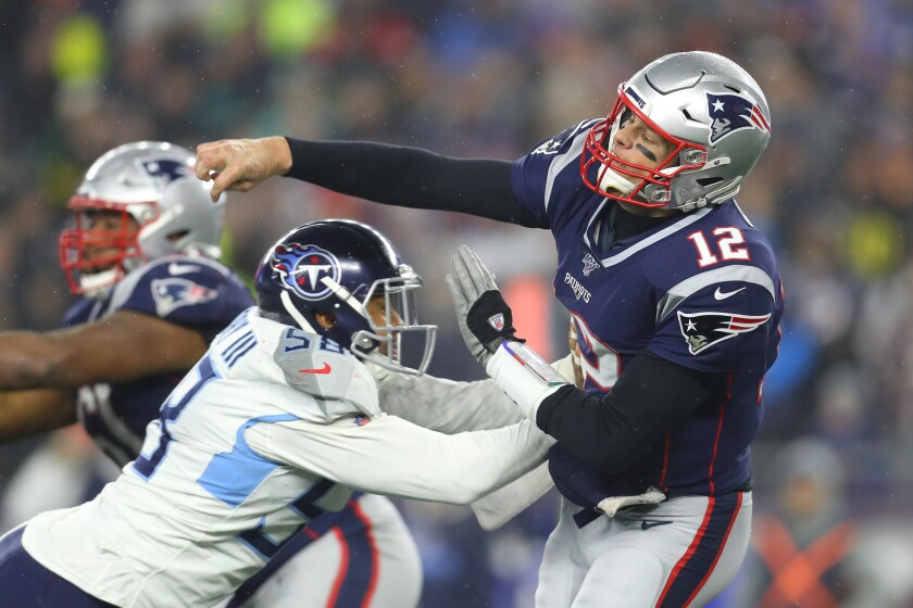 Patriots quarterback Tom Brady passes while being pressured by Titans linebacker Harold Landry in the second half Saturday night.