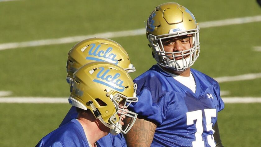 UCLA center Boss Tagaloa and fellow linemen