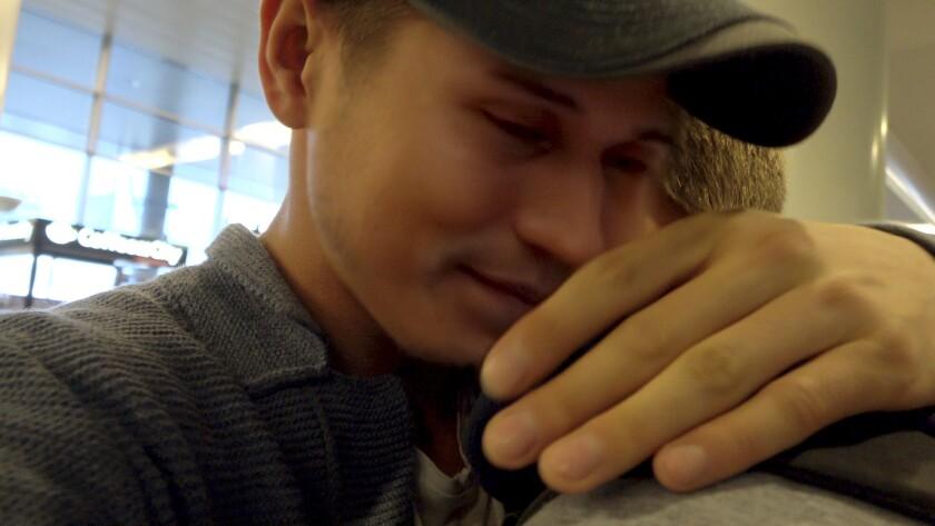 "A gay Russian man, alias ""Grisha,"" reunites with his boyfriend, alias ""Bogdan,"" in the documentary ""Welcome to Chechnya."""