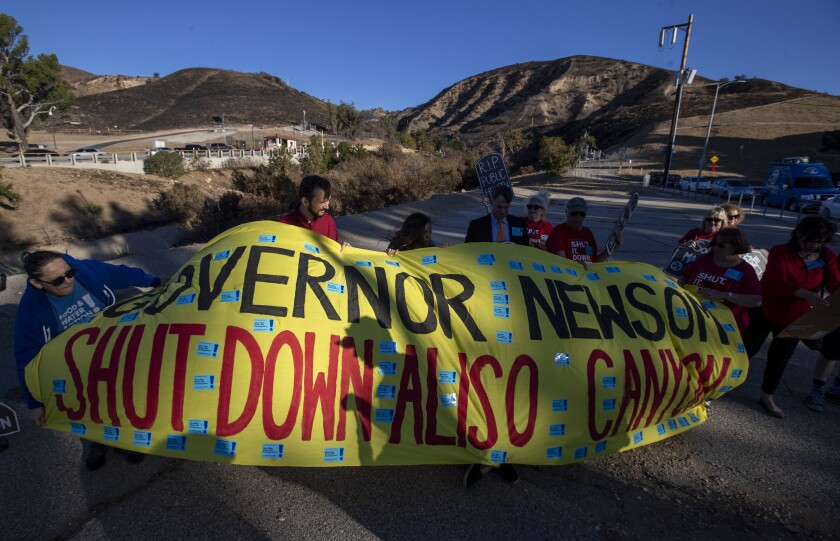 Protesters unfurl a banner in Porter Ranch marking the fourth anniversary of the Aliso Canyon methane blowout in 2019.