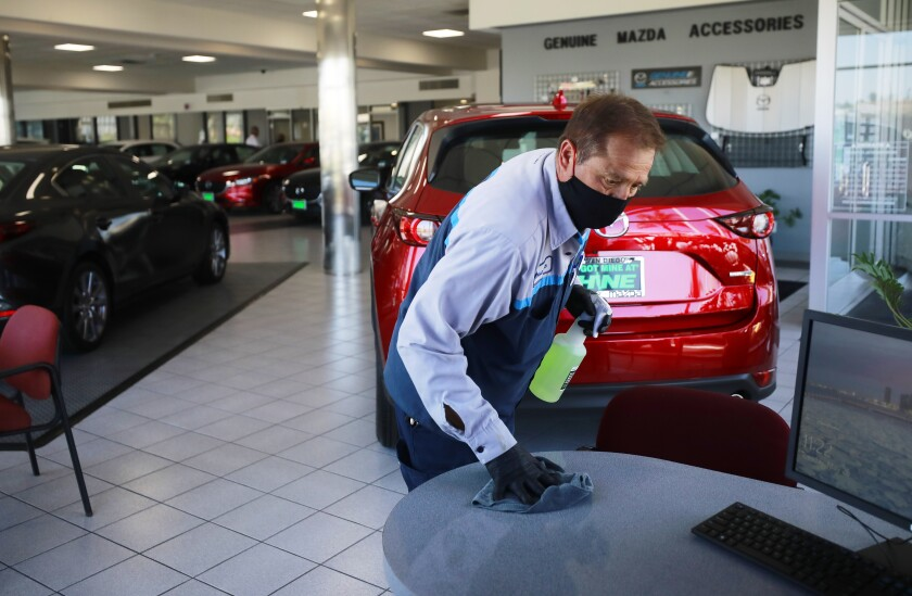 An employee at John Hine Mazda in Mission cleans surfaces.