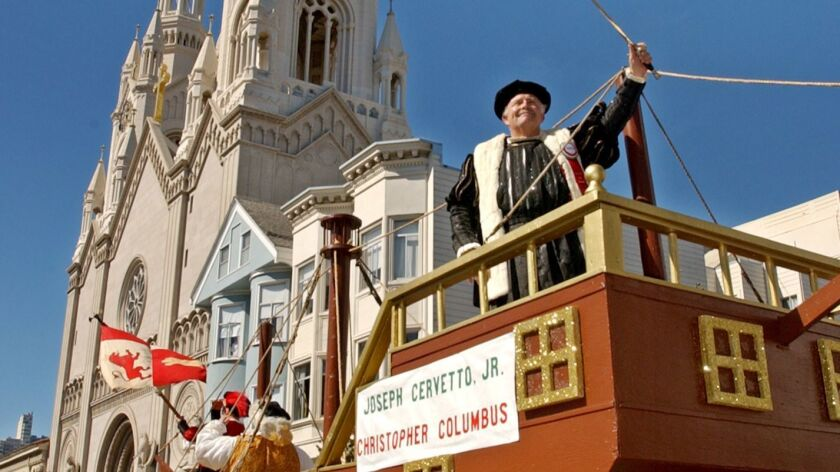 Joseph Cervetto Jr. holds up a sword while dressed as Christopher Columbus on a float during San Francisco's Italian Heritage Parade in 2003.