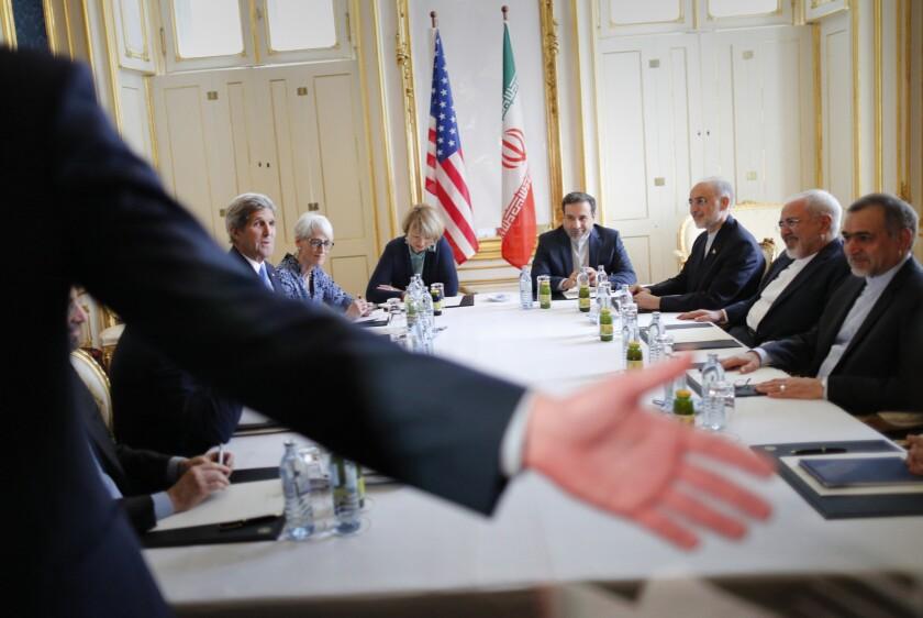 Un agente de seguridad mueve la mano para pedir a los reporteros que partan de una sala donde el secretario de Estado de Estados Unidos John Kerry (izquierda) se reunía con el ministro de Relaciones Exteriores iraní Mohammad Javad Zarif (segundo desde la derecha), en un hotel en Viena, Austria, el miércoles 1 de julio de 2015. (Carlos Barria /Pool vía AP)