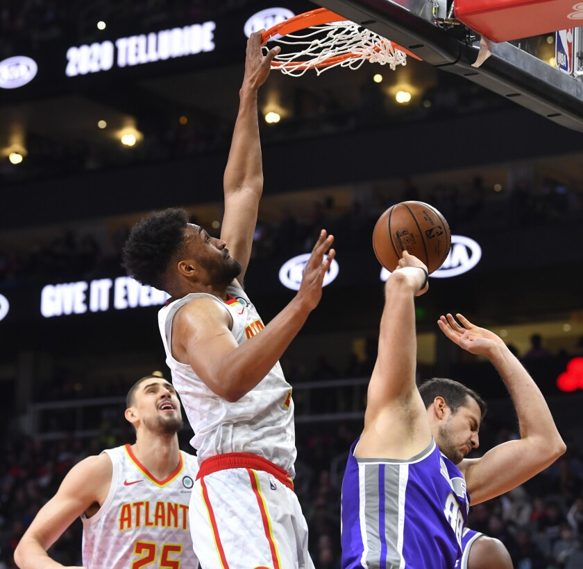 Atlanta Hawks forward Jabari Parker dunks against Sacramento Kings forward Nemanja Bjelica, right, of Serbia, during the first half of an NBA basketball game Friday, Nov. 8, 2019, in Atlanta. (AP Photo/John Amis)