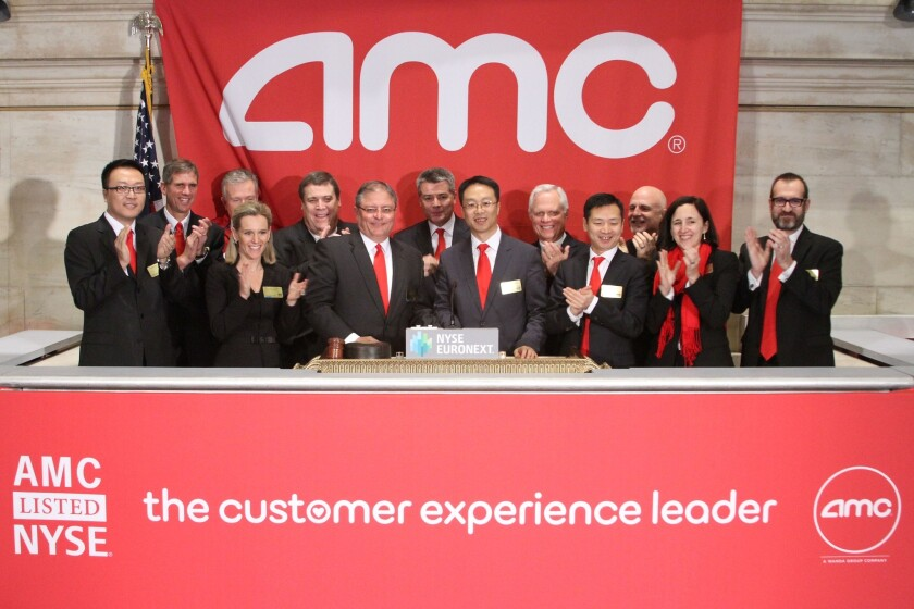 AMC Entertainment CEO Gerry Lopez, sixth from left, rings the opening bell Tuesday at the New York Stock Exchange, where AMC began trading its shares.