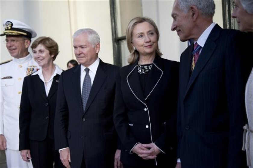 U.S. Secretary of State Hillary Rodham Clinton, second from right, talks with Governor of Victoria David de Kretser, right, as they pose for photographs with, from left, Chairman of the Joint Chiefs of Staff Adm. Michael Mullen, his wife Debrah Mullen, and U.S. Secretary of Defense Robert Gates before a reception at Government House on Sunday, Nov. 7, 2010 in Melbourne, Australia. (AP Photo/Evan Vucci, Pool)