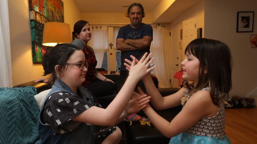 Sisters Lucca, left, and Maya Reinoso play at home in Chicago as their parents Carrie and Mario are
