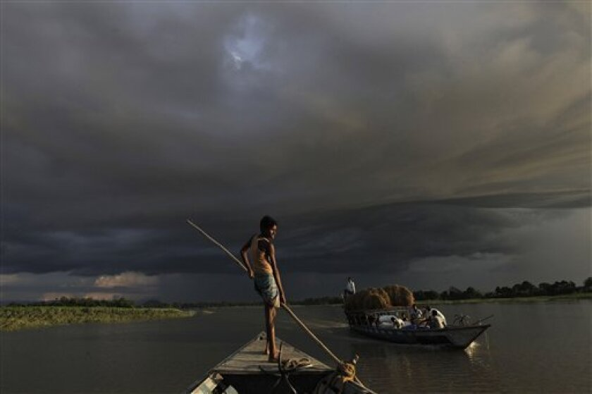 A boat carries flood relief materials as monsoon clouds surrounded the flood affected Gagalmari village in Assam state, India, Monday, July 2, 2012. The floods from monsoon rains in northeastern India killed dozens of people, with more than 2,000 villages inundated as rivers breached their banks, a