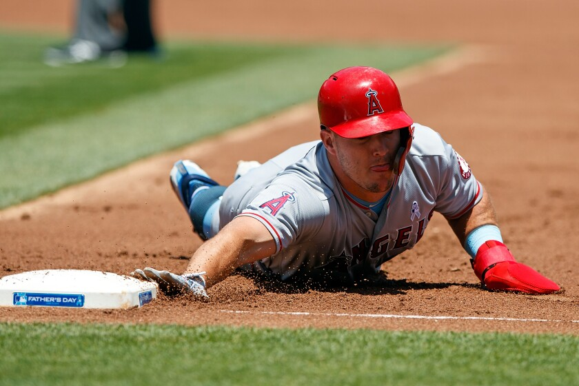 Angels center fielder Mike Trout slides back to first base during a game.