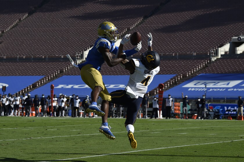 UCLA defensive back Jay Shaw, left, deflects a pass intended for California wide receiver Nikko Remigio.