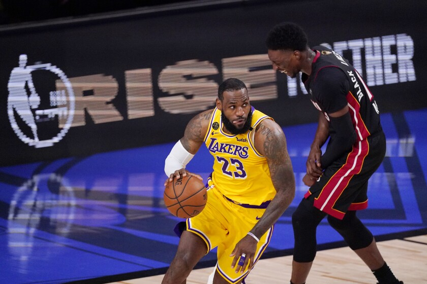 Los Angeles Lakers' LeBron James (23), left, takes the ball as Miami Heat's Bam Adebayo (13) winces during Game 1 of basketball's NBA Finals Wednesday, Sept. 30, 2020, in Lake Buena Vista, Fla. Adebayo had to leave the game with a left shoulder strain. (AP Photo/Mark J. Terrill)