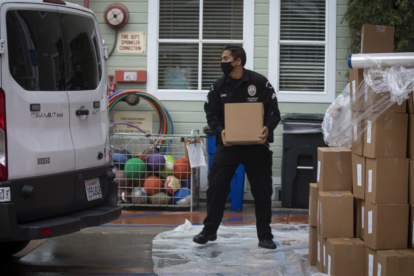 LAPD Officer Anthony Lopez transfers supplies to be delivered to home-bound seniors in Hollywood on Thursday.