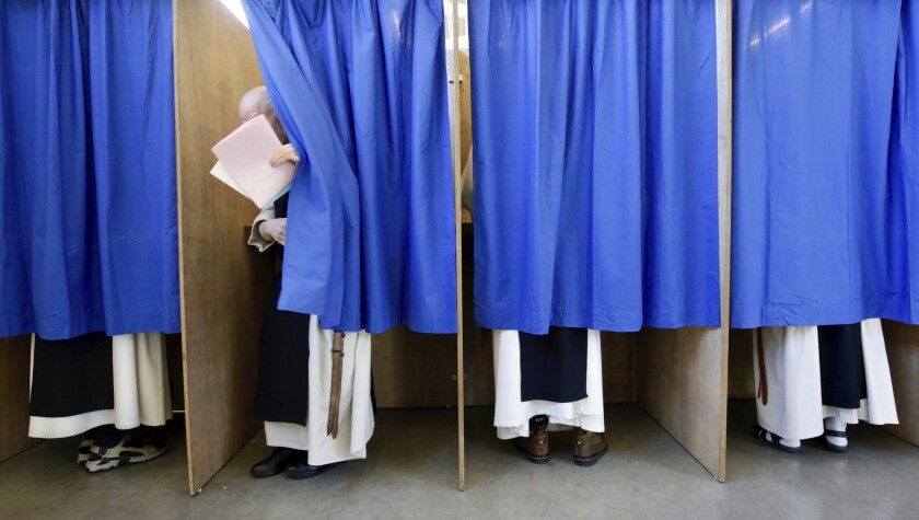 Monks from the Saint Sixtus Trappist Abbey cast their votes behind curtains at a polling station in Westvleteren, Belgium, Sunday, May 26, 2019. Belgium, which has one of the oldest compulsory voting systems, goes to the polls Sunday to vote on the regional, federal and European level. (AP Photo/Olivier Matthys)