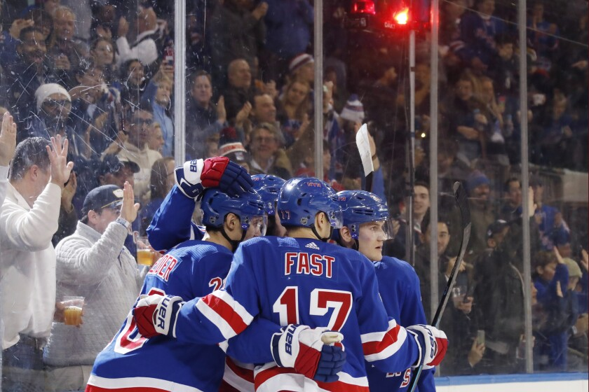 Teammates celebrate with New York Rangers left wing Chris Kreider, left, after Kreider scored a goal during the second period of an NHL hockey game against the Anaheim Ducks, Sunday, Dec. 22, 2019, in New York. It was Kreider's second goal of the game.(AP Photo/Kathy Willens)