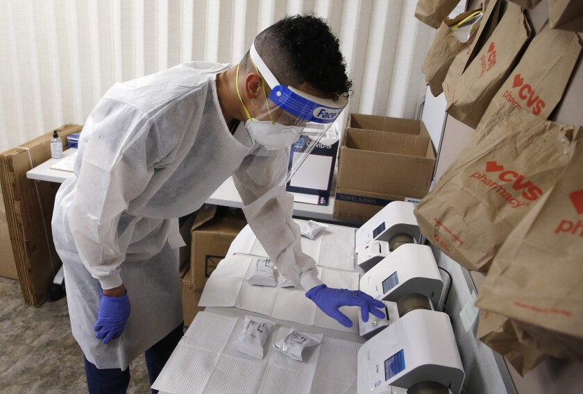 Berto Cortez, a CVS pharmacy technician, shows how COVID-19 tests are processed in a testing area set up by CVS at St. Vincent de Paul medical clinic, Monday, June 15, 2020, in Phoenix. The Arizona Department of Health Services posted on its website Monday another 1,104 cases of COVID-19 and eight additional deaths, bringing the statewide total number of coronavirus cases to 36,705 and related deaths to 1,194. (AP Photo/Ross D. Franklin)