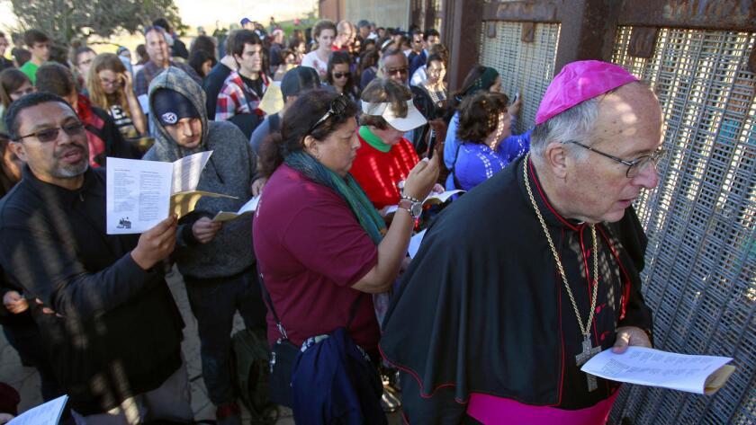 El obispo Robert McElroy y una multitud de personas cantan para quienes están al otro lado de la frontera entre los EE.UU. y México.