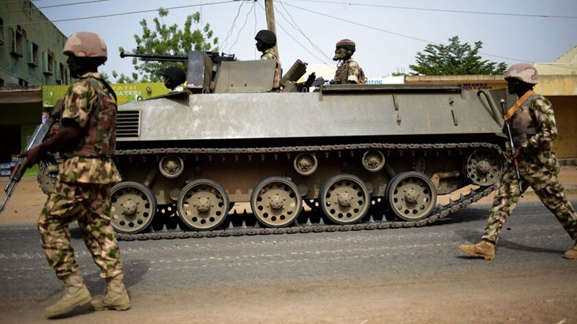 In this photo taken Monday March 9, 2015, Nigerian troops patrol in the north-eastern Nigeria city o