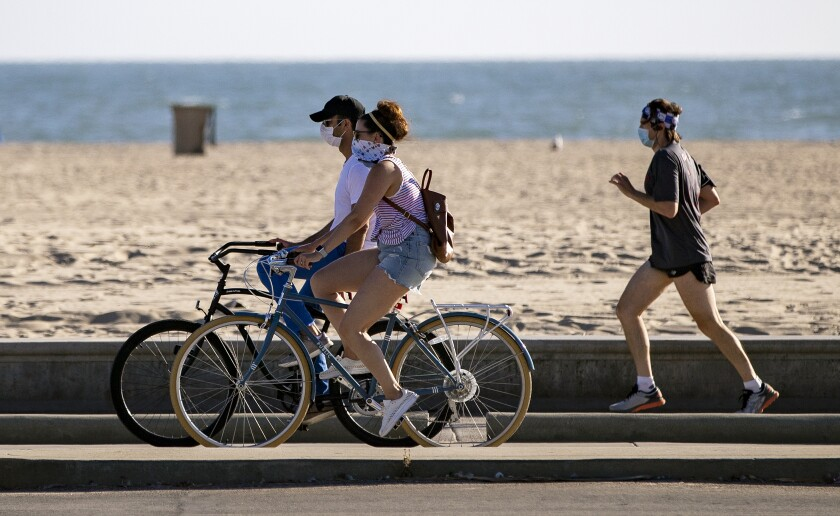 Bicyclists and a runner wear masks as they enjoy the boardwalk at Santa Monica Beach