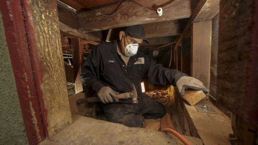 Arturo Gonzalez of Seismic Safety company of Pasadena, bolt and brace a house foundation to make it