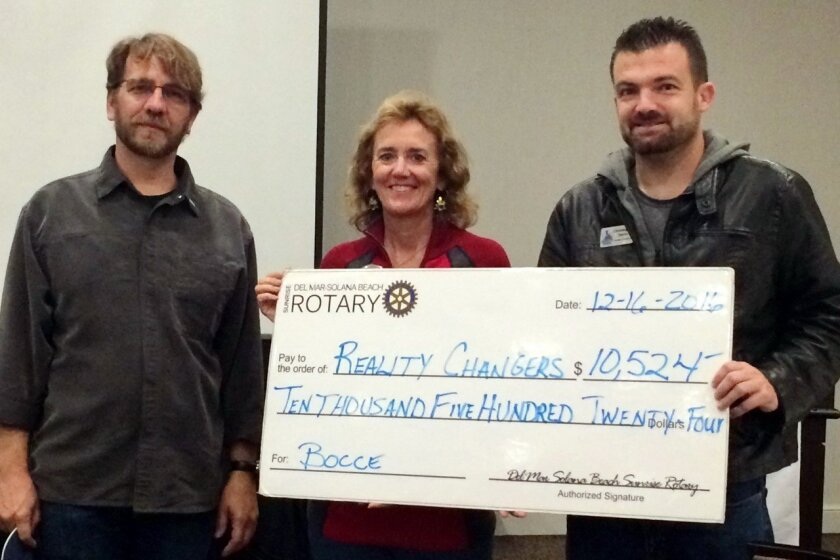 From left, Del Mar-Solana Beach Rotary Club president Liam Murphy and community service chairperson Susan Hennenfent present Reality Changers' founder and president, Chris Yanov, with a check.