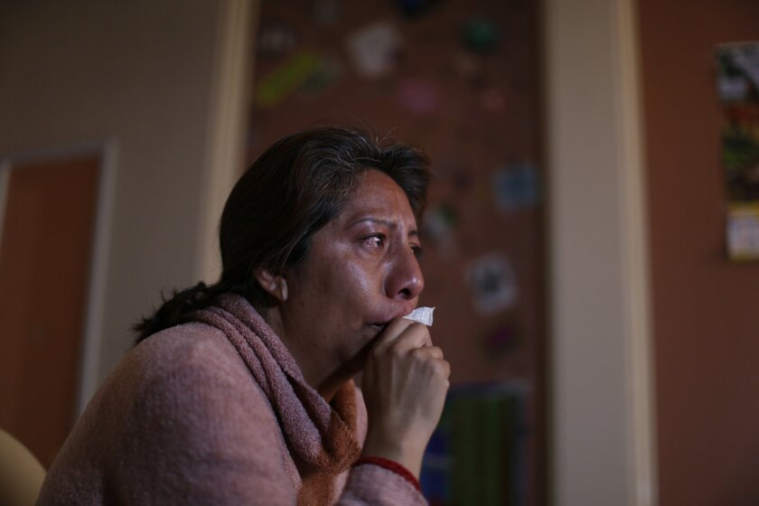 In this Jan. 25, 2016 photo, Guadalupe Reyes holds back her tears as she talks about her daughter Mariana Yanez, in Ecatepec, a rough neighborhood on the outskirts of Mexico City. On an otherwise normal evening in September 2014, Yanez left her home saying she was going to make some photocopies, an