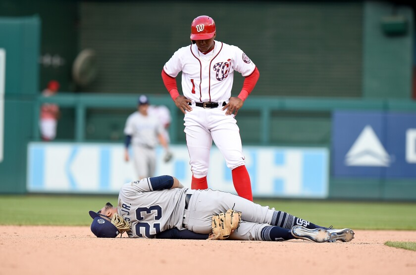 Wilmer Difo of the Washington Nationals looks on as Fernando Tatis Jr. of the Padres is injured on a play in the 10th inning at Nationals Park on Sunday.