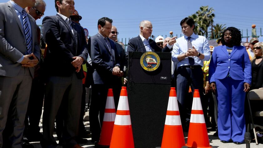 Assembly Speaker Anthony Rendon, left, Gov. Jerry Brown and then-Senate President pro Tem Kevin de León take part in a 2017 rally for a bill that raised the gas tax.