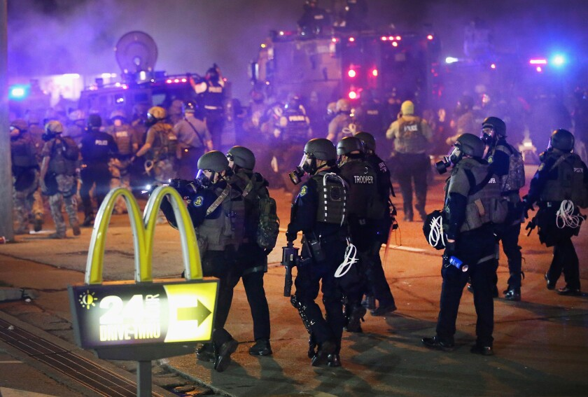Officers in riot gear walk past a McDonald's drive-thru sign during protests in Ferguson, Mo.