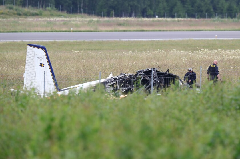 """Police officers investigate the wreckage of a plane outside Orebro Airport in Orebro, Sweden, Friday, July 9, 2021. Police in Sweden say nine people were killed when a small plane carrying skydivers crashed on Thursday night. A spokesperson for the Swedish Maritime Administration, which oversees air traffic, told broadcaster SVT the crash must have occurred """"in connection"""" with the plane's takeoff. (Jeppe Gustafsson/TT News Agency via AP)"""