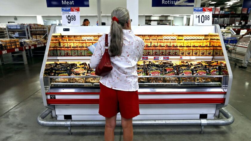 A woman looks at a refrigerated case in the meat section of a grocery store.