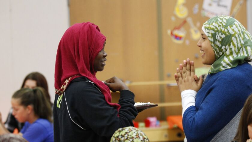 Rufaida Sulieman, 14, left, and Ayat Alchamoual, 14, share a laugh during a Thanksgiving meal for refugees and their families put on by San Diego Refugee Tutoring at Ibarra Elementary School on Tuesday, Nov. 21, 2017.