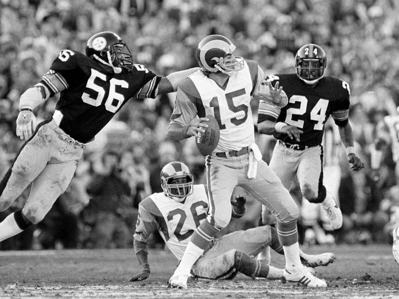 Rams quarterback Vince Ferragamo (15) prepares to pass but never gets the ball past Steelers' Robin Cole (56), during Super Bowl XIV action at the Rose Bowl in Pasadena on Jan. 21, 1980. Ferragamo is sacked on the play. The Rams lost to the Steelers, 31-19.