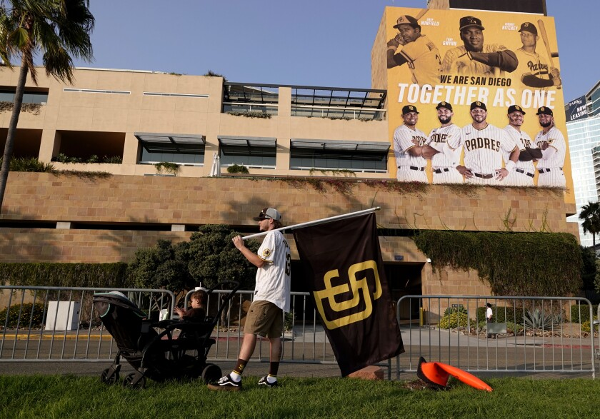 Padres fan Dominic Norton holds a flag outside of Petco Park as he shows support for team following game last September.