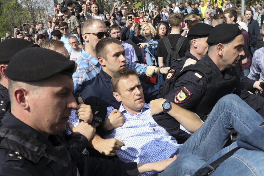 FILE - In this May 5, 2018, file photo, Russian police carry opposition leader Alexei Navalny, center, from a demonstration against President Vladimir Putin in Pushkin Square in Moscow, Russia. Attempts over the years to silence Kremlin critic Navalny have all failed so far. Now Navalny is in a coma in a Berlin hospital after suffering what German authorities say was a poisoning with a chemical nerve agent while traveling in Siberia on Aug. 20. (AP Photo, File)