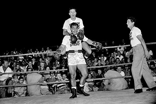 "Comedian Jerry Lewis, who predicted he would be ""right on top"" of heavyweight champ Rocky Marciano in their exhibition bout in Hollywood on Nov. 18, 1954, does just that to the amusement of several hundred kids who watched the ""fight"" at Paramount Studio. Lewis' comedy partner, Dean Martin, referees the bout at right. The playful bout was staged in advance of that year's Muscular Dystrophy Assn. fund drive. Many of the young spectators had MD."