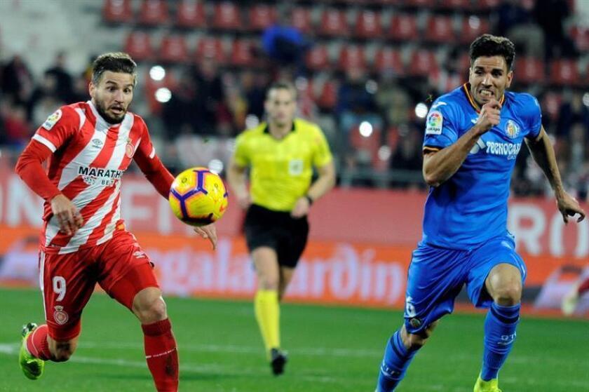 El centrocampista del Girona FC, Cristian Portugués (i), persigue el balón ante el defensa del Getafe CF, Leandro Cabrera, durante el encuentro disputado esta tarde en el Campo Municipal Montillivi de Girona. EFE