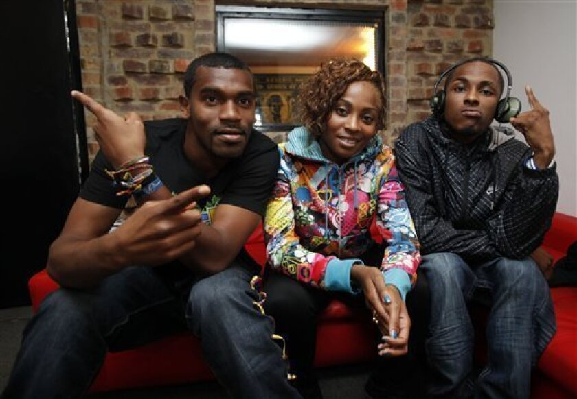"""In this photo taken Jan. 8, 2011, Carlos Valencia, """"Tostao,"""" left, Gloria Martinez, """"Goyo,"""" center, and Miguel Martinez, """"Slow,"""" of the Colombian hip-hop group ChocQuibTown, pose for a photo during an interview with The Associated Press in Bogota, Colombia.  ChocQuibTown are Grammy nominees for Bes"""